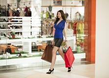 Härliga hållande shoppingpåsar för ung kvinna som går i shoppa royaltyfria foton