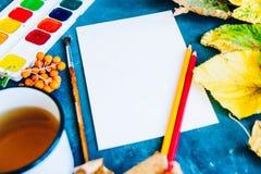 Härliga höstsidor, borstar, målarfärg och ark på ett mörker tillbaka arkivfoton