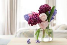 Härliga hyacinter i exponeringsglasvas på tabellen inomhus, utrymme för text arkivfoton