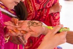 Härliga indiska kvinnor som applicerar mehendi till en turist Royaltyfri Foto