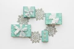 Härliga julgåvor och silversnöflingor som isoleras på vit bakgrund Turkos färgade slågna in xmas-askar royaltyfri fotografi