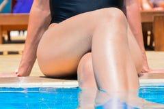 Härliga kvinnaben som solbadar nära simbassäng Arkivbild