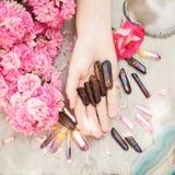 Härliga kvinnahänder med den perfekta violeten spikar polerar på vit träbakgrund som rymmer små kvartskristaller fotografering för bildbyråer