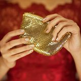 Härliga kvinnahänder med perfekt spikar den skönhethandväskan eller plånboken för polermedel den hållande royaltyfria foton