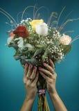 Härliga kvinnahänder rymmer en stor bukett av rosor royaltyfria foton