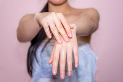 Härliga kvinnahänder som applicerar kräm Arkivfoto
