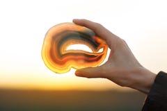 Härliga kvinnahänder som rymmer agat, skivar kristallen i solljuset arkivfoton