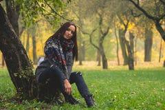 Härliga kvinnan som den har, vilar under träd Ensam kvinna som tycker om naturlandskap i höst arkivbild