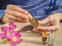 Härliga kvinnas händer som rymmer en liten liten medicinflaska av parfymerad olja Arabisk Attar royaltyfria foton