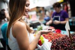 Härliga kvinnashoppinggrönsaker och frukter på marknaden royaltyfri fotografi