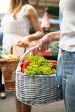 Härliga kvinnashoppinggrönsaker och frukter på marknaden arkivbilder