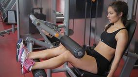 Härliga kvinnaskakor lägger benen på ryggen muskler på en simulator lager videofilmer