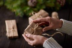 Härliga kvinnliga händer är den packade julgåvan i brunt kraft papper royaltyfria foton