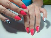 Härliga kvinnliga händer med färgrikt spikar, spikar arkivbild