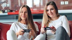 Härliga kvinnliga lyckliga vänner som spelar videospel på konsolen stock video