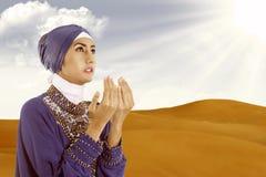 Härliga kvinnliga muslim som ber i blått på öknen fotografering för bildbyråer