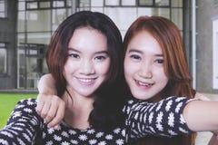 Härliga kvinnliga studenter som tillsammans tar ett foto royaltyfria bilder