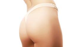 Härliga kvinnligbakdelar i beige underbyxor Fotografering för Bildbyråer