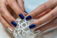 Härliga kvinnlighänder med blå manikyr arkivbilder