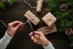Härliga kvinnlighänder med sax som klipps av repet, julgåvor i brunt kraft papper Royaltyfri Foto