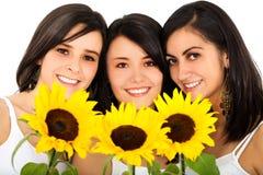 härliga kvinnligvänner som rymmer solrosor Arkivfoto