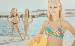 Härliga kvinnor i bikini på sjösidan Fotografering för Bildbyråer