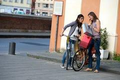 Härliga kvinnor i staden med cyklar och påsar Arkivfoton