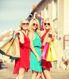 Härliga kvinnor med shoppingpåsar i det ctiy Arkivfoto