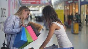 Härliga kvinnor med shoppingvagnen nära supermarket som serching för något Arkivbild