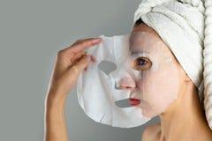 Härliga kvinnor som applicerar den ansikts- maskeringen med fuktighetsbevarande hudkräm royaltyfri bild