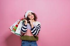 Härliga kvinnor som bär ljus jul som bär färgrika shoppa påsar På rosa bakgrund Julshopping och royaltyfria bilder