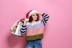 Härliga kvinnor som bär ljus jul som bär färgrika shoppa påsar På rosa bakgrund Julshopping och fotografering för bildbyråer