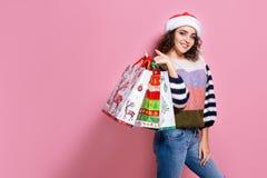 Härliga kvinnor som bär ljus jul som bär färgrika shoppa påsar På rosa bakgrund Julshopping och arkivbilder