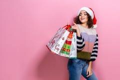 Härliga kvinnor som bär ljus jul som bär färgrika shoppa påsar På rosa bakgrund Julshopping och arkivfoto