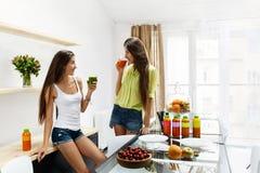 Härliga kvinnor som dricker den nya detoxen Juice For Healthy Nutrition royaltyfria bilder