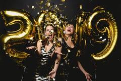 Härliga kvinnor som firar nytt år Lyckliga ursnygga flickor i stilfulla sexiga partiklänningar som rymmer guld- 2019 ballonger fotografering för bildbyråer