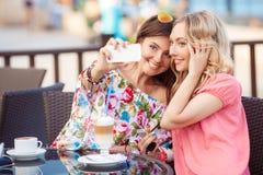 Härliga kvinnor som fotograferar en telefon Royaltyfri Bild