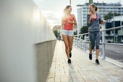 Härliga kvinnor som joggar i solnedgång arkivfoto