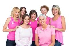 Härliga kvinnor som poserar och bär rosa färger för bröstcancer Arkivbilder