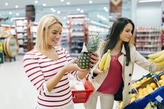 Härliga kvinnor som shoppar grönsaker och frukter Royaltyfria Bilder