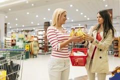 Härliga kvinnor som shoppar grönsaker och frukter Arkivbild