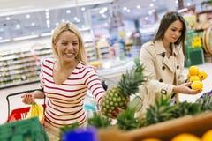 Härliga kvinnor som shoppar grönsaker och frukter Arkivbilder