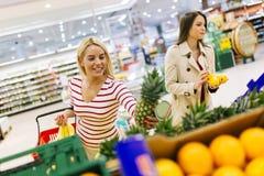 Härliga kvinnor som shoppar grönsaker och frukter Royaltyfri Foto