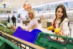 Härliga kvinnor som shoppar grönsaker och frukter Arkivfoto