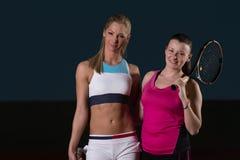 Härliga kvinnor som spelar tennis och ser lyckliga Arkivfoton