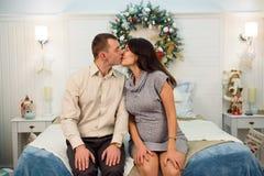 Härliga kyssande gravida par som är förälskade på jul och att ha, vilar på jul ferier för det nya året bifokal royaltyfria foton