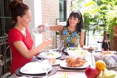Härliga latinamerikanska kvinnor som tillsammans tycker om ett utomhus- hem- mål Royaltyfri Bild