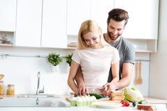 Härliga le par som tillsammans lagar mat i ett modernt kök arkivfoto
