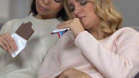 Härliga ledsna flickor som äter choklader som sitter tillsammans att lugna och att koppla av, pms lager videofilmer