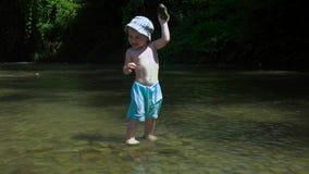 Härliga Little Boy kastar kiselstenar i en bergflod stock video
